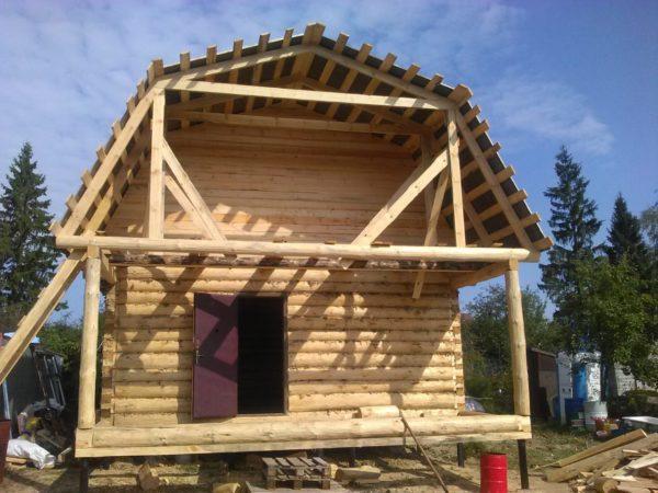 Сруб дома с мансардной крышей и верандой